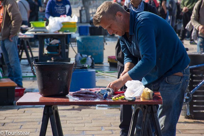 Fisherman cleaning fish at Marseille market