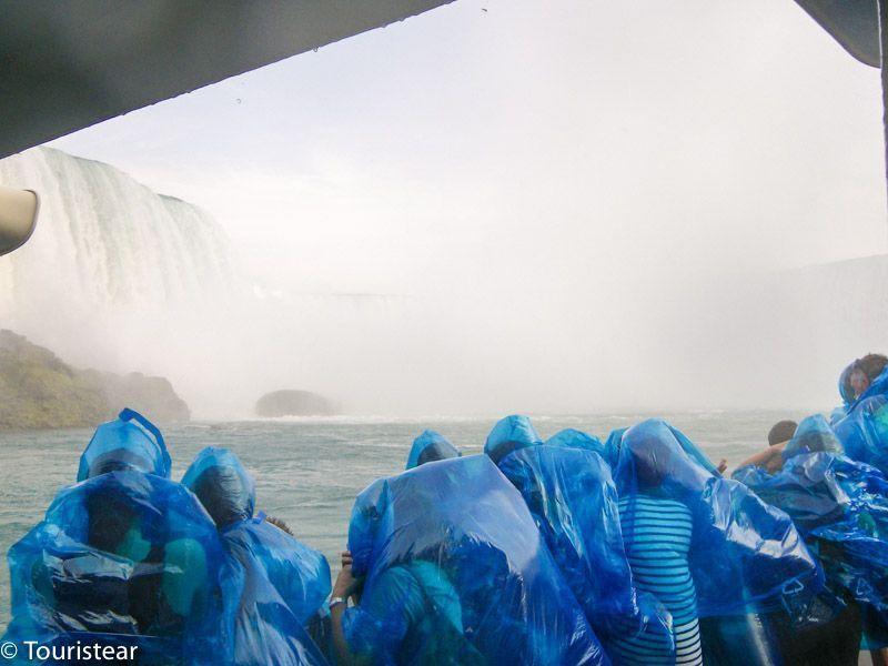 Las cataratas del niágara desde el barco y la gente con los típicos chubasqueros azules